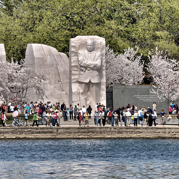 MLK Memorial across tidal basin cherry blossoms with a crowd of people